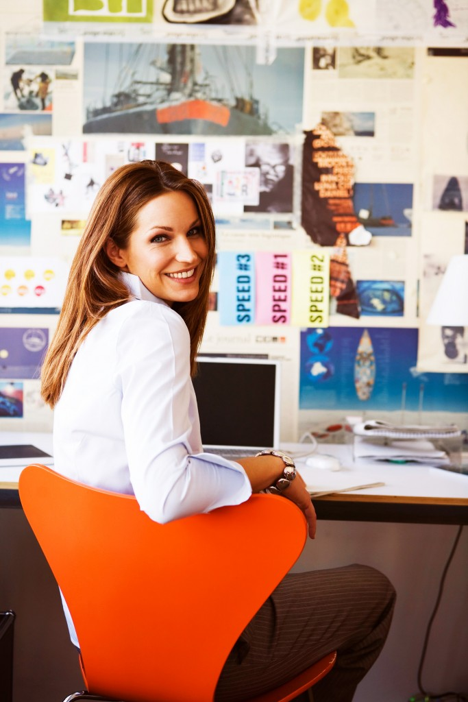 Business woman in office sitting at desk, smiling